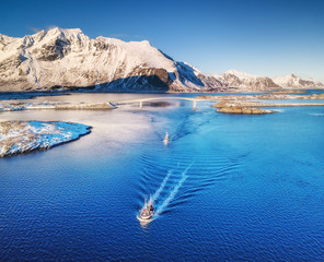 Aerial view of fishing boats, bridge, mountains and ocean. Boats on the Lofoten islands, Norway. Ocean and mountains in The Norway. Travel image in Norway.