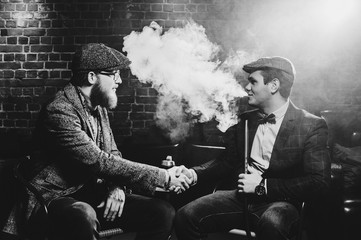 Retro portrait of two friends smoking hookah in a bar. black and white view.