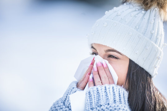 Attractive young woman blowing her nose with a tissue in winter