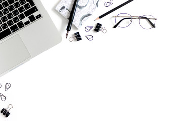 Workspace with laptop, glasses, stationery on a white background