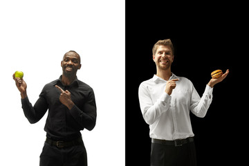 Men eating a hamburger and fresh fruits on a black and white background. The happy afro and caucasian men. The burger, fast, healthy and unhealthy food concept