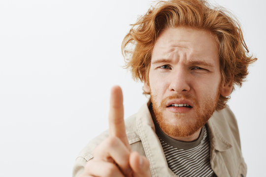 Headshot of confused and questioned funny redhead with messy hair and beard squinting while bending towards and poking camera with index finger unsure and suspicious frowning uncertain