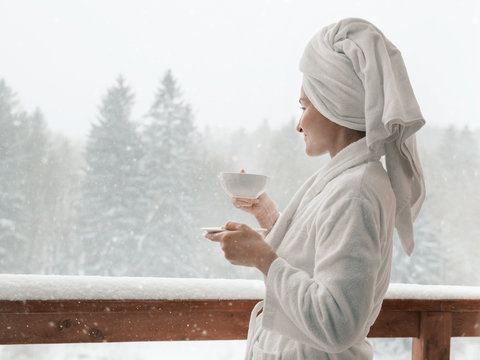 Young woman on the balcony holding a cup of coffee in the morning. She in hotel room looking at the nature in winter. She is with the bath towel on her head an wearing bath coat.