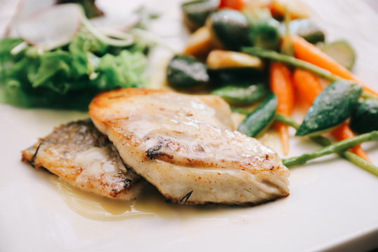 Sea bass fillet with grilled vegetables and salad on wooden table