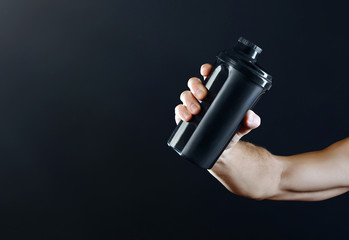 Arm of a muscular sportman  with a black shaker on a dark background.
