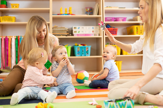 Group of babies in nursery. Nursery teacher and assistant play with kids
