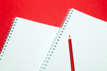 Notepadand red pensil blank sheets in cage white paper on spring on red background. Concept free space, copyspace, business book, diary, use for notes at art seminar, conference, lesson, lecture