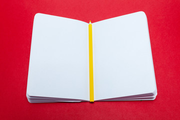 Closeup notepad and yellow pencil with blank sheets white paper on red background. Concept free space, copyspace, business book, diary, notes at professional seminar, conference, lesson, lecture