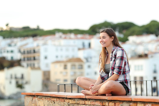 Happy teen contemplating views sitting on a ledge