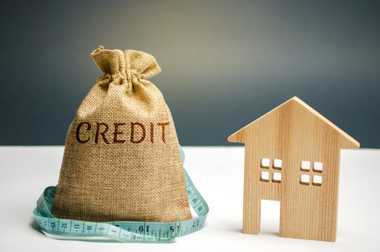 A bag with money and a tape measure and the word credit and a wooden house. Lack of money to pay the loan. Mortgage for housing. Savings and accumulation of money. Buying a property in debt. Poverty