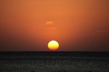 Tramonto con luce arancione sul mare di Aruba, mar dei Caraibi