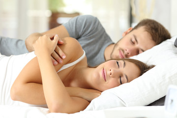 Couple sleeping together at hotel or home