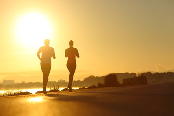 Couple practicing sport running at sunset on the road