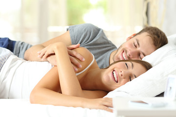 Happy couple in love sleeping together on bed