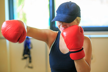 Beautiful mature blonde woman in tracksuit and cap is engaged in red boxing gloves in the gym. Sports training.