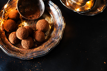 vegan chocolate truffles - dessert for the New Year's Eve, carnival against the background of silverware, elegant, vintage. On a dark background.