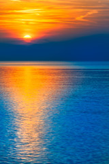 Gorgeous End of Day at the Sea / Natural spectacle - colorful blue and orange reflecting sunset at sea horizon (copy space)