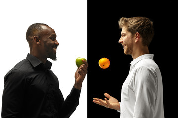 Men eating a fresh fruits on a black and white background. The happy smiling afro and caucasian men. The healthy food and diet concept