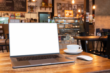 Blank screen laptop with mouse and coffee cup on wooden table in coffe shop.