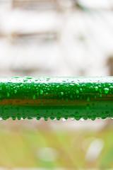 Raindrops on green metal tube. Regentropfen auf Metallrohr.