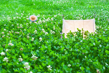 Romantic Summer´s Eve at Camping / Small vintage illuminated miniature canvas tent at wide meadow of clover plants, back of teddy bear with straw hat tranquil dreamy between leaves (copy space)