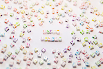Conceptual of Motivational Happy Sunday Words made with Colorful Alphabetical Beads