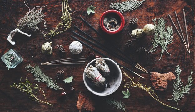 Various air element objects to use in witchcraft and wicca on a witch's altar filled with evergreens dried herbs sage incense sticks for smoke cleansing