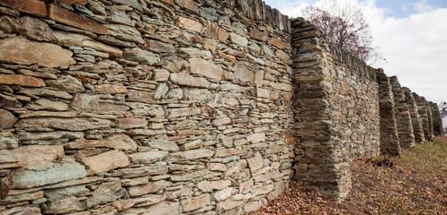 Historische Steinmauer mit Laub. Historic stone wall with greenery.