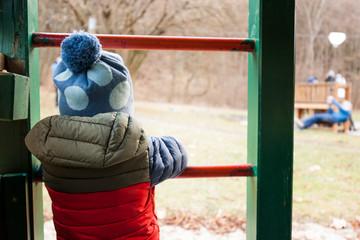 Einsames Kind schaut auf Spielplatz. Lonely kid looking on playground.