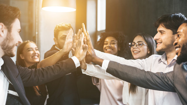 High-five for success. Diverse group of business colleagues in office