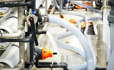 Large industrial water treatment and boiler room. Plastic and metal pipes with armature, valves