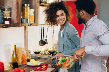 Vegetarian african-american couple cooking salad in kitchen
