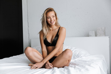 Amazing beautiful young woman in lingerie underwear at morning sitting in bed at home.