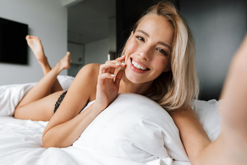 Image of pretty woman 20s wearing luxury lingerie smiling and taking selfie, while lying in bed on white linen in modern apartment
