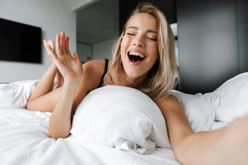 Image of relaxed woman 20s wearing luxury lingerie smiling and taking selfie, while lying in bed on white linen in modern apartment