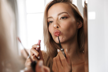Young woman in lingerie underwear looking at mirror apply her lipstick lip gloss doing makeup.