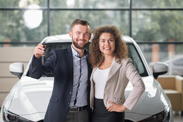Happy couple posing with new white car and keys.
