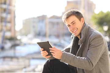 Happy man holds a tablet and looks at camera