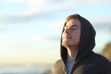 Teenage man breathing fresh air on the beach