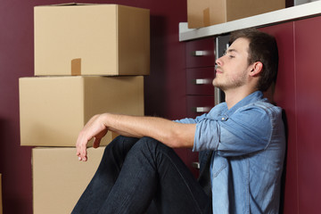 Sad man moving home sitting in the kintchen floor