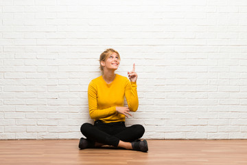 Young girl sitting on the floor pointing a great idea and looking up