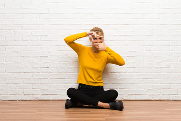 Young girl sitting on the floor focusing face. Framing symbol