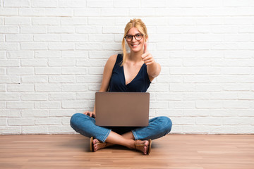 Blonde girl sitting on the floor with her laptop giving a thumbs up gesture and smiling on white brick wall background