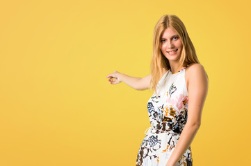 Blonde young girl in a summer dress pointing back with the index finger presenting a product on yellow background