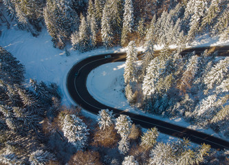 road in winter mountain landscape. Aerial view of forest
