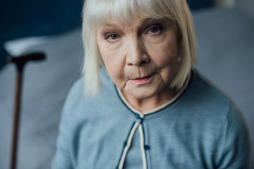 portrait of sad senior woman with grey hair looking at camera at home