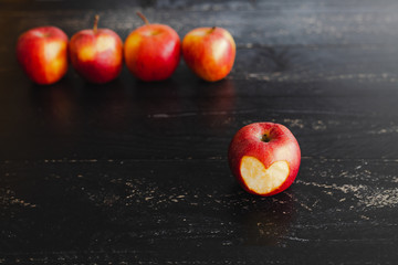 group of red apples with different tones on dark wooden table