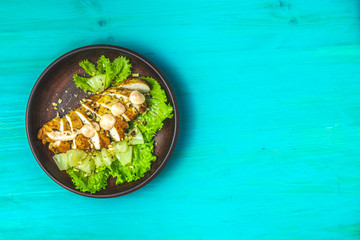 Delicious salad in ceramic plate on a blue turquoise table