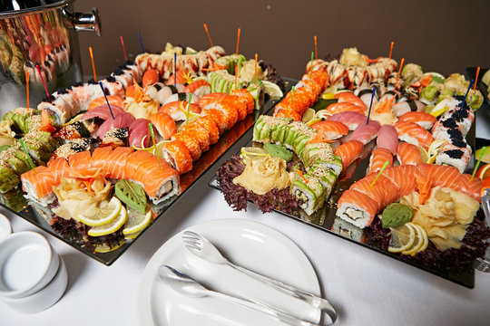 Decorated catering banquet table with different sushi rolls and nigiri sushi plate assortment on a party