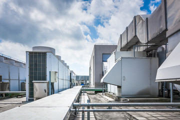 Square air-conditioning unit on the roof with a round fan. In the background gradually receding other units that are out of focus. On the right side light blue sky and commercial space. Wall mural